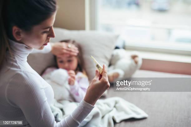 messen sie die temperatur am kranken kind. - ansteckende krankheit stock-fotos und bilder