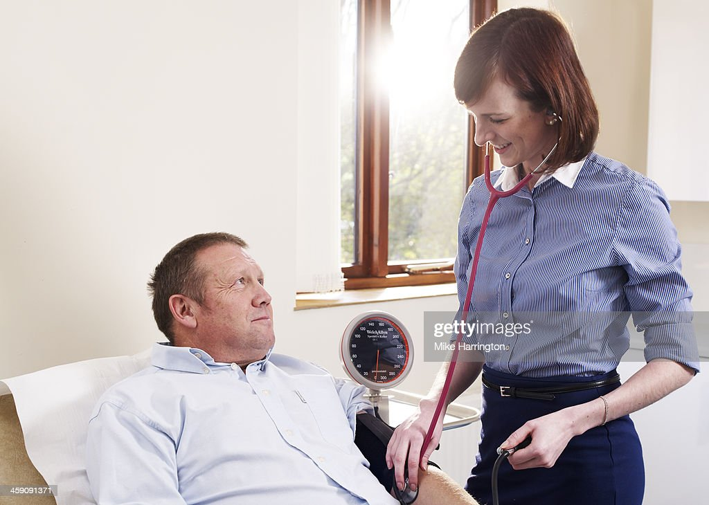 GP measuring blood pressure of patient in surgery. : Stock Photo