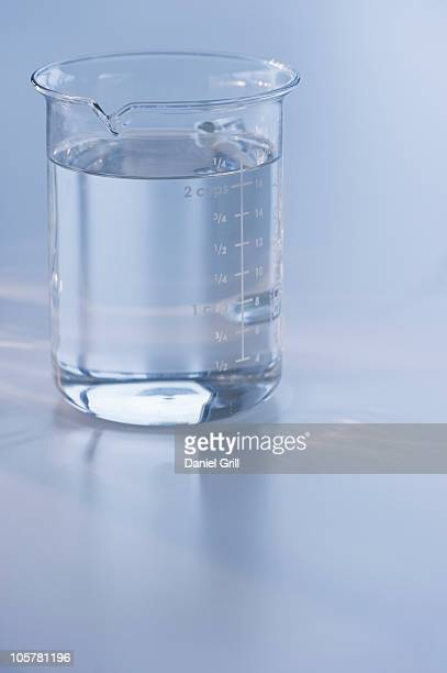 measuring cup full of water - measuring cup stock pictures, royalty-free photos & images