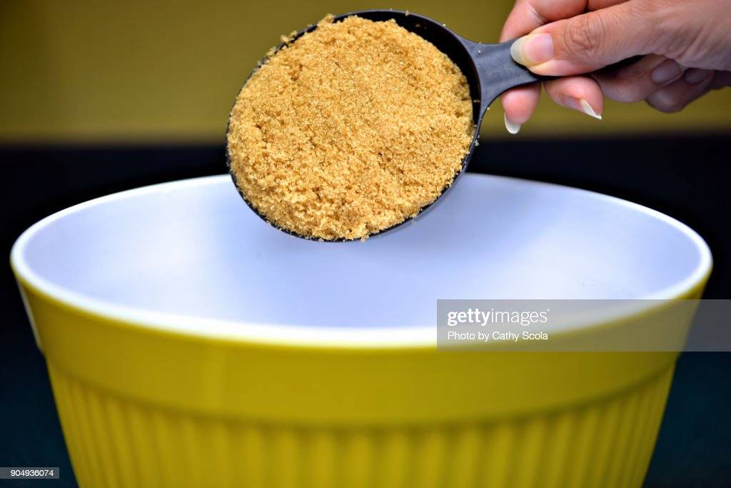 Measuring cup of brown sugar : Stock Photo