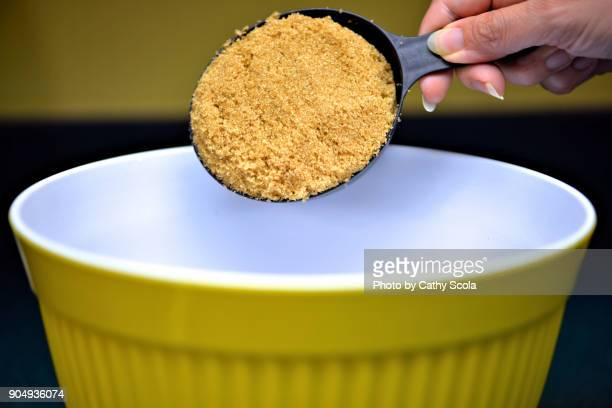 adding measuring cup brown sugar into