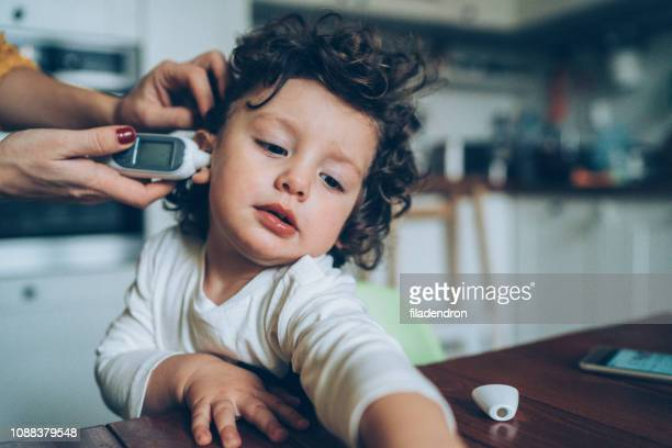 measuring little boy's temperature - fever stock pictures, royalty-free photos & images