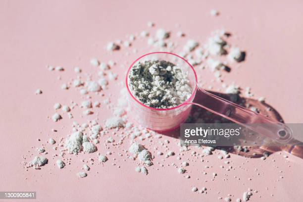 measuring spoon with collagen powder or alginate mask on pink background - 白粉 ストックフォトと画像