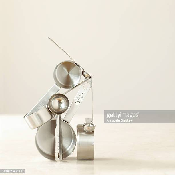 measuring spoons and cups balancing on top of each other - measuring spoon stock pictures, royalty-free photos & images