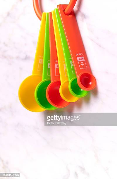 measuring spoons hanging on kitchen wall - measuring spoon stock pictures, royalty-free photos & images