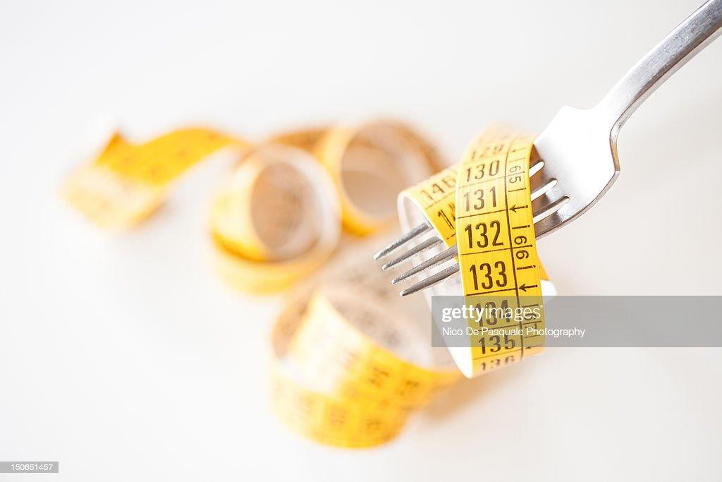 Measuring tape around fork : Stock Photo