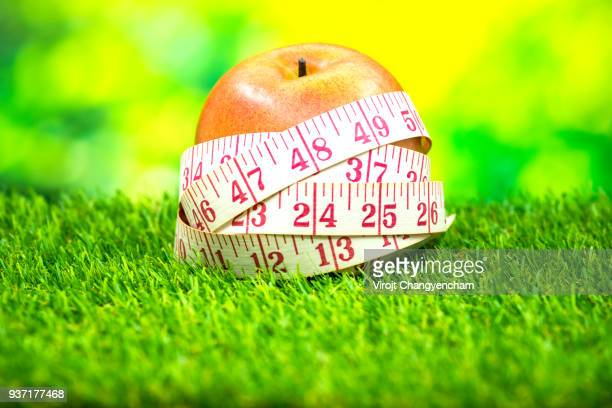 measuring tape around red apple on the green grass, for healthy diet concept