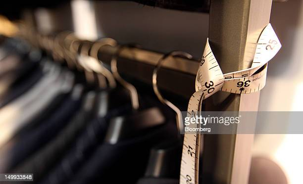 A measuring tape hangs from a rack of suits at the Gieves Hawkes store owned by Trinity Ltd on Saville Row in London UK on Tuesday Aug 7 2012 UK...