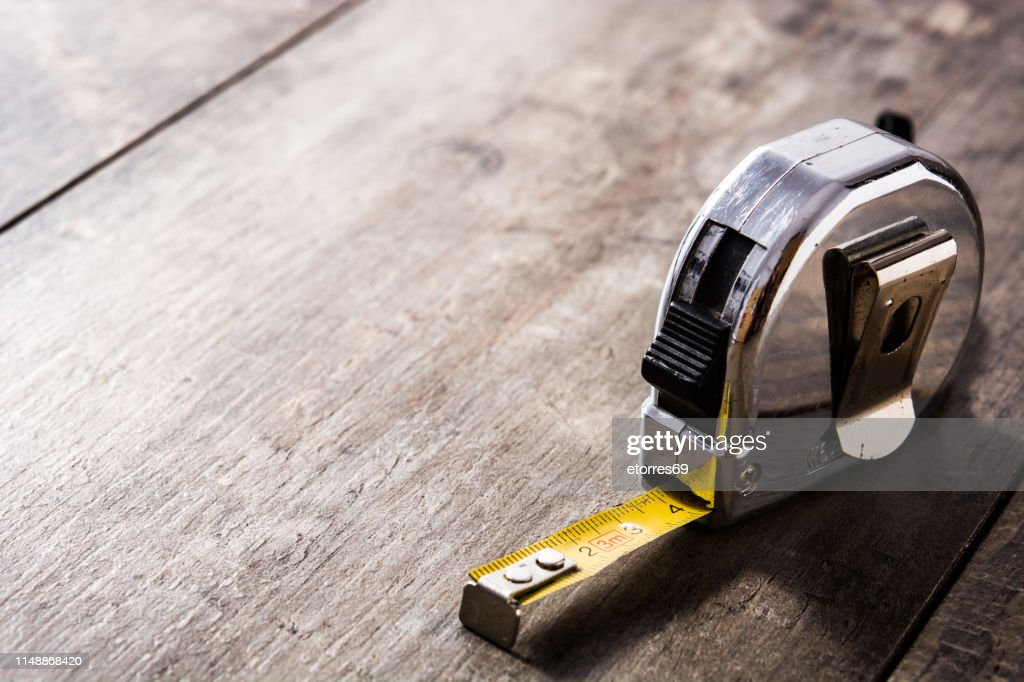 Measuring tape on wooden table : Stock Photo