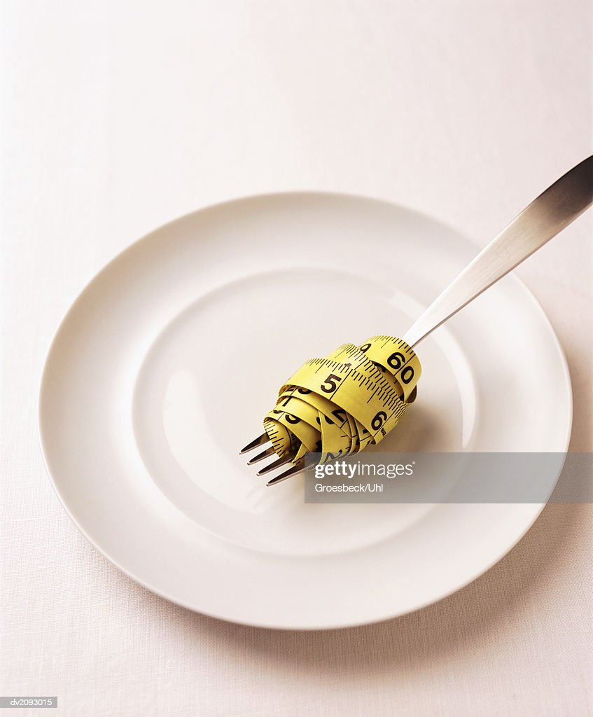 Measuring Tape Wrapped Around a Fork on a Plate : Stock Photo