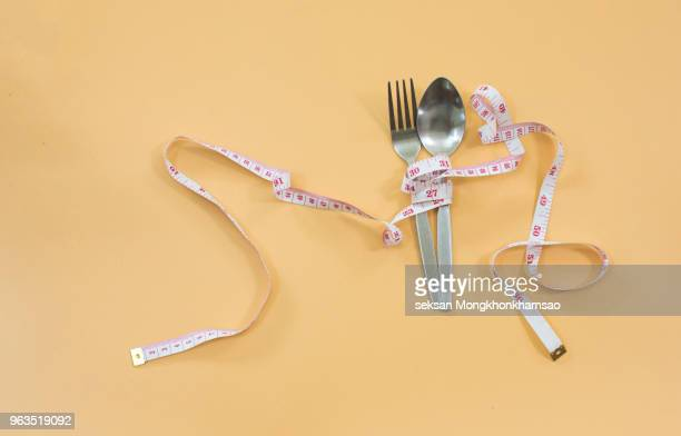 measuring tape wrapped around fork lying on color surface. diet concept - fat people eating donuts stock pictures, royalty-free photos & images