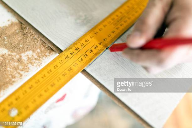 measuring the board for next cut - inch stock pictures, royalty-free photos & images