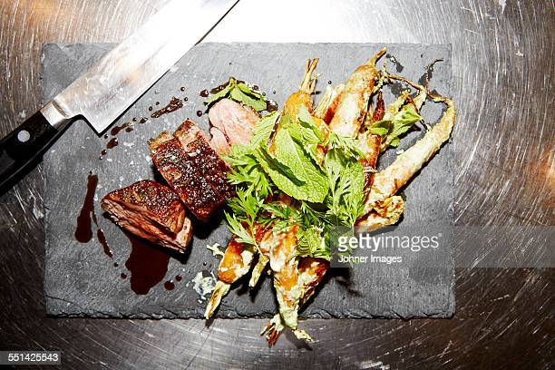 Meat and herbs on chopping board