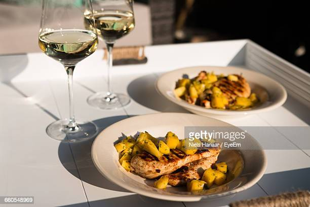 Meat And Mango In Plates By Wineglasses