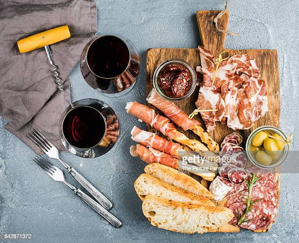 Meat appetizer selection. Salami, prosciutto, bread sticks, baguette, olives and sun-dried tomatoes, two glasses of red wine over grey concrete textured backdrop