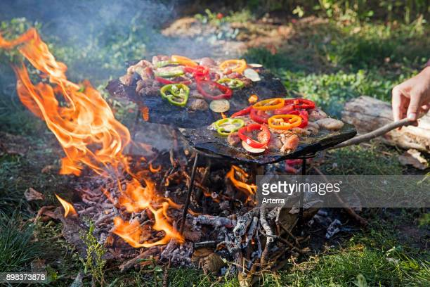 Meat bell peppers and vegetables cooked on a traditional stone barbecue in Kyrgyzstan