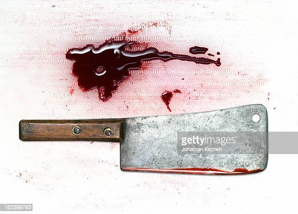 A meat cleaver and blood on a chopping board