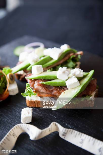Meat, feta and avocado open sandwiches on slate