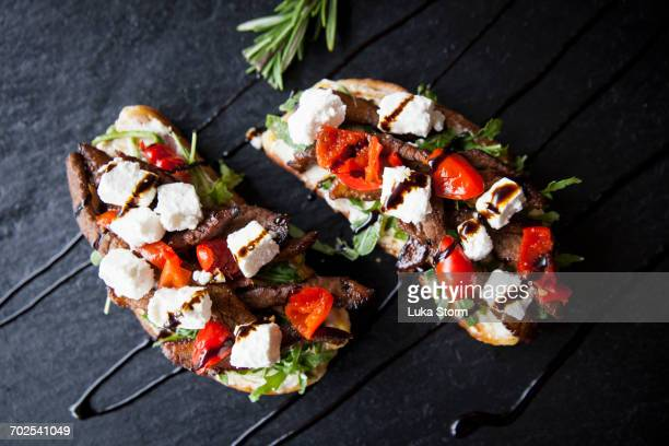 Meat, feta and tomato open sandwiches with sauce garnish on slate