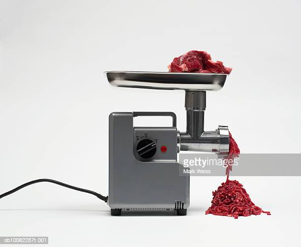Meat grinder with meat against white background