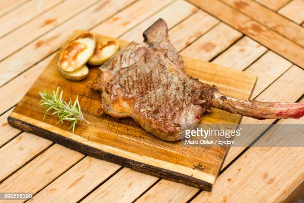 Meat On Cutting Board Over Wooden Table