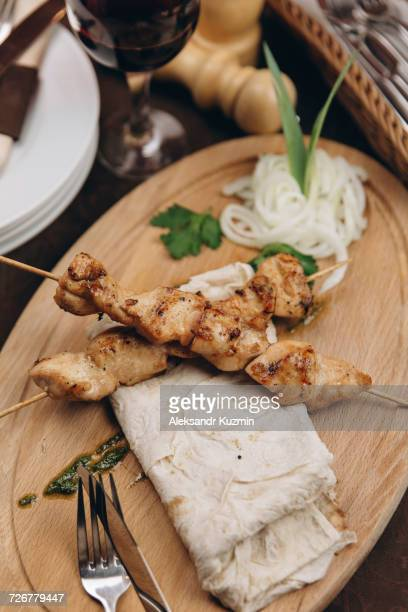 Meat on skewers with bread on tray