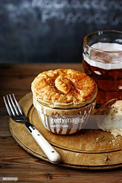 meat pie on bread board with pint of bitter