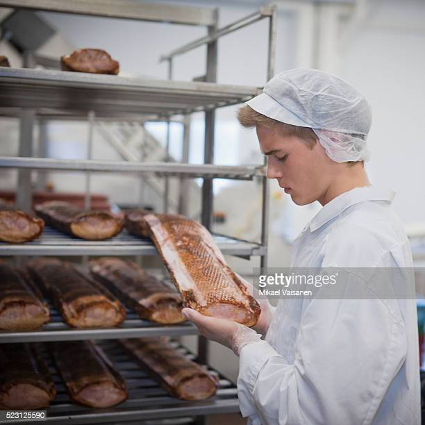 meat processing plant worker examining a piece of - meat processing plant stock pictures, royalty-free photos & images