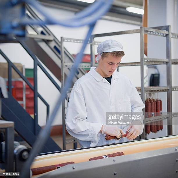 meat processing plant worker packaging sausage - meat processing plant stock pictures, royalty-free photos & images