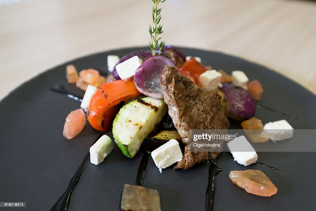 Meat with vegetables and cheese in restaurant : Photo