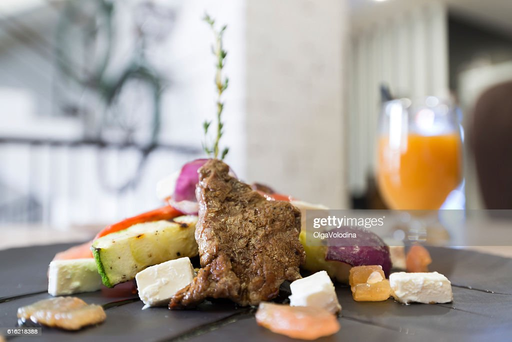 Meat with vegetables and cheese in restaurant : Stock-Foto