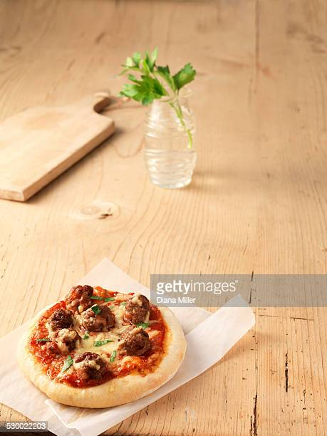Meatball and cheese pizza on greaseproof paper