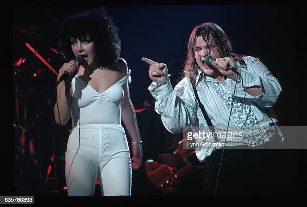 Meatloaf on stage performing with Karla Devito They are shown in a 3/4length view He is pointing toward the audience Photograph 1978