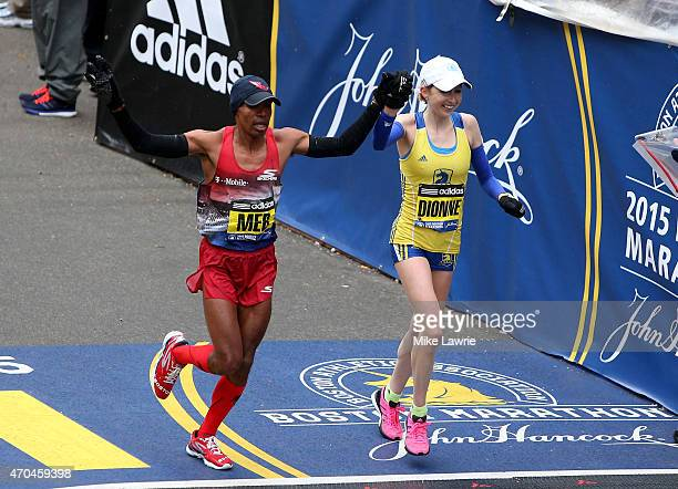 Meb Keflezighi of the United States and Hilary Dionne of the United States run toward the finish line during the 119th Boston Marathon on April 20...