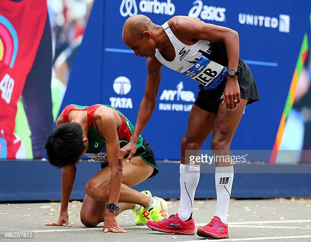 Meb Keflezighi of the United States assists Yuki Kawauchi of Japan after he crossed the finish line during the TCS New York City Marathon on November...