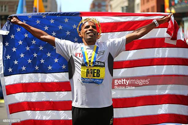 Meb Keflezighi of the United States holds up an American flag at the finish line and wears his crown and medal during his victory ceremony after...