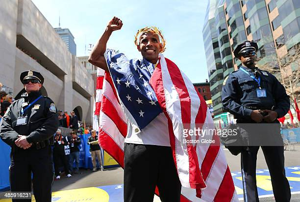 Meb Keflezighi of the United States wears an American flag around his shoulders at the finish line during his victory ceremony after finishing first...