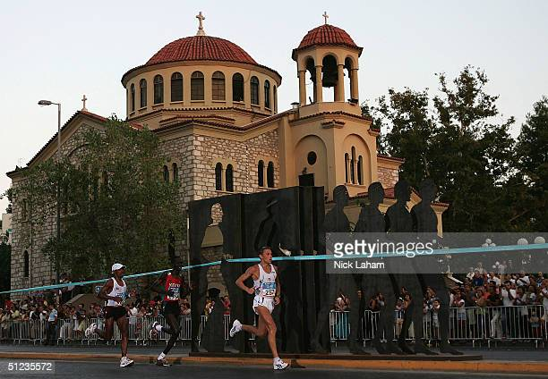 Mebrahtom Keflezighi of the United States, Paul Tergat of Kenya and Stefano Baldini of Italy run past a church in the men's marathon on August 29,...