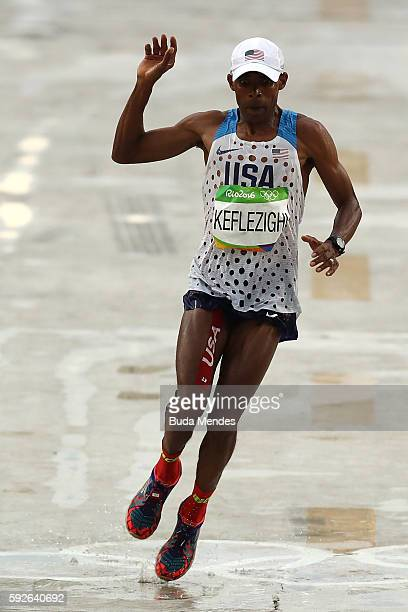 Mebrahtom Keflezighi of the United States slips as he crosses the finish line during the Men's Marathon on Day 16 of the Rio 2016 Olympic Games at...