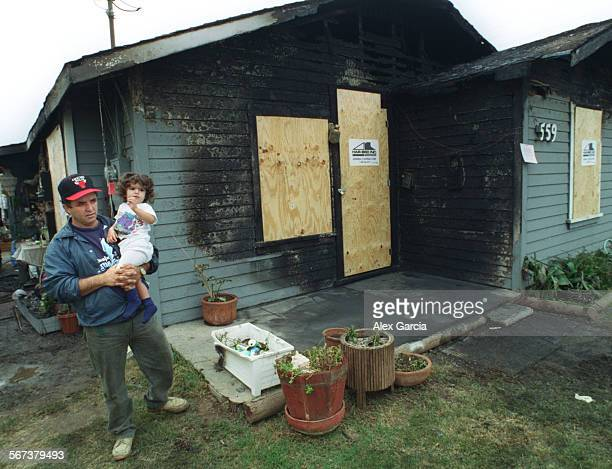 MEburnt house1016AAG––Costa Mesa resident Ramon Gutierrez and daughter Leslie take a look of their next–door neighbor's house that was heavily...