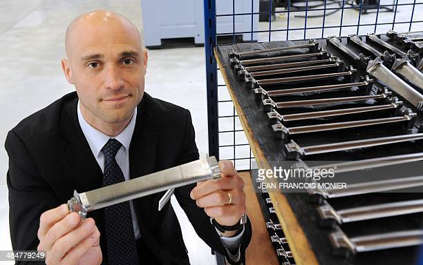 Mecachrome's French Chief Executive Officer Arnaud de Ponnat presents a TiAi turbine blade for the new jet engine LEAP of SNECMA on April 14 2014 at...