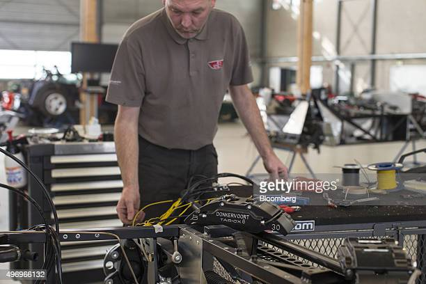 A mechanic adjusts the electronic wiring on the steel chassis frame of a Donkervoort D8 GTO automobile at the Donkervoort Automobielen BV...