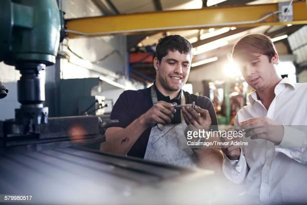Mechanic and customer examining parts in auto repair shop