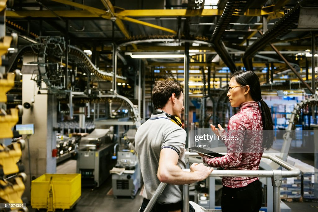 Mechanic And Female Engineer Talking in Factory : Stock Photo