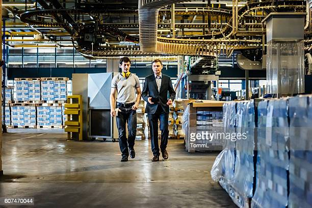 Mechanic and Manager talking and walking in factory