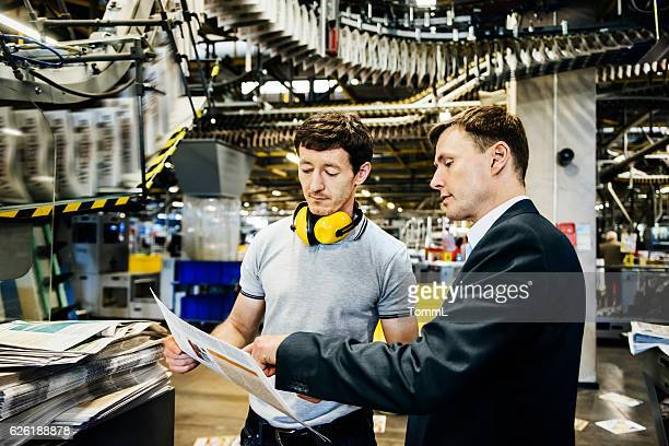 Mechanic and Manager talking in a printery