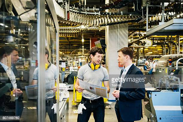 Mechanic and Manager talking in huge factory