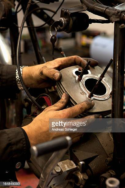 Mechanic attaching cylinder to motorcycle
