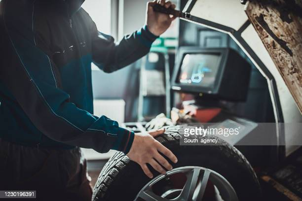 mechanic balancing a tire in auto repair shop - wheel stock pictures, royalty-free photos & images