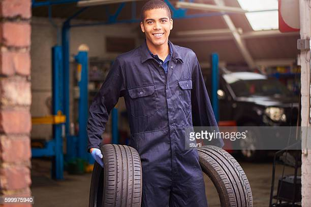 Mechanic carrying two tyres